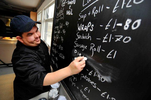 Unity worker marks up the menu on a blackboard